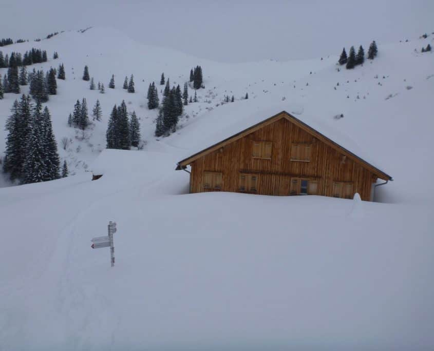 Mountain hut halfway covered in snow