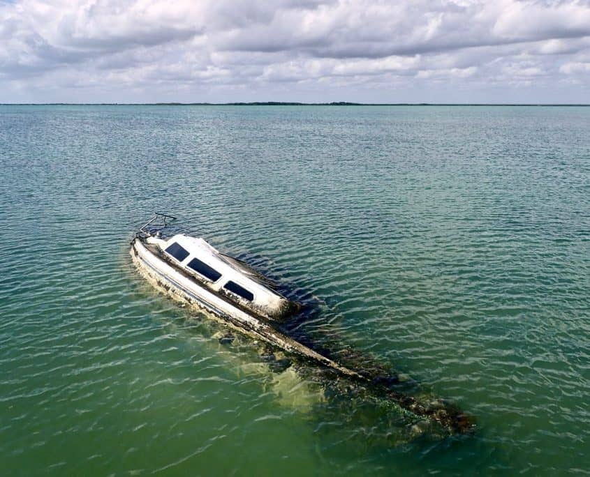 Ccling through Sian Ka'an Biosphere Reserve - sunken sailing boat at the jetty in Punta Allen